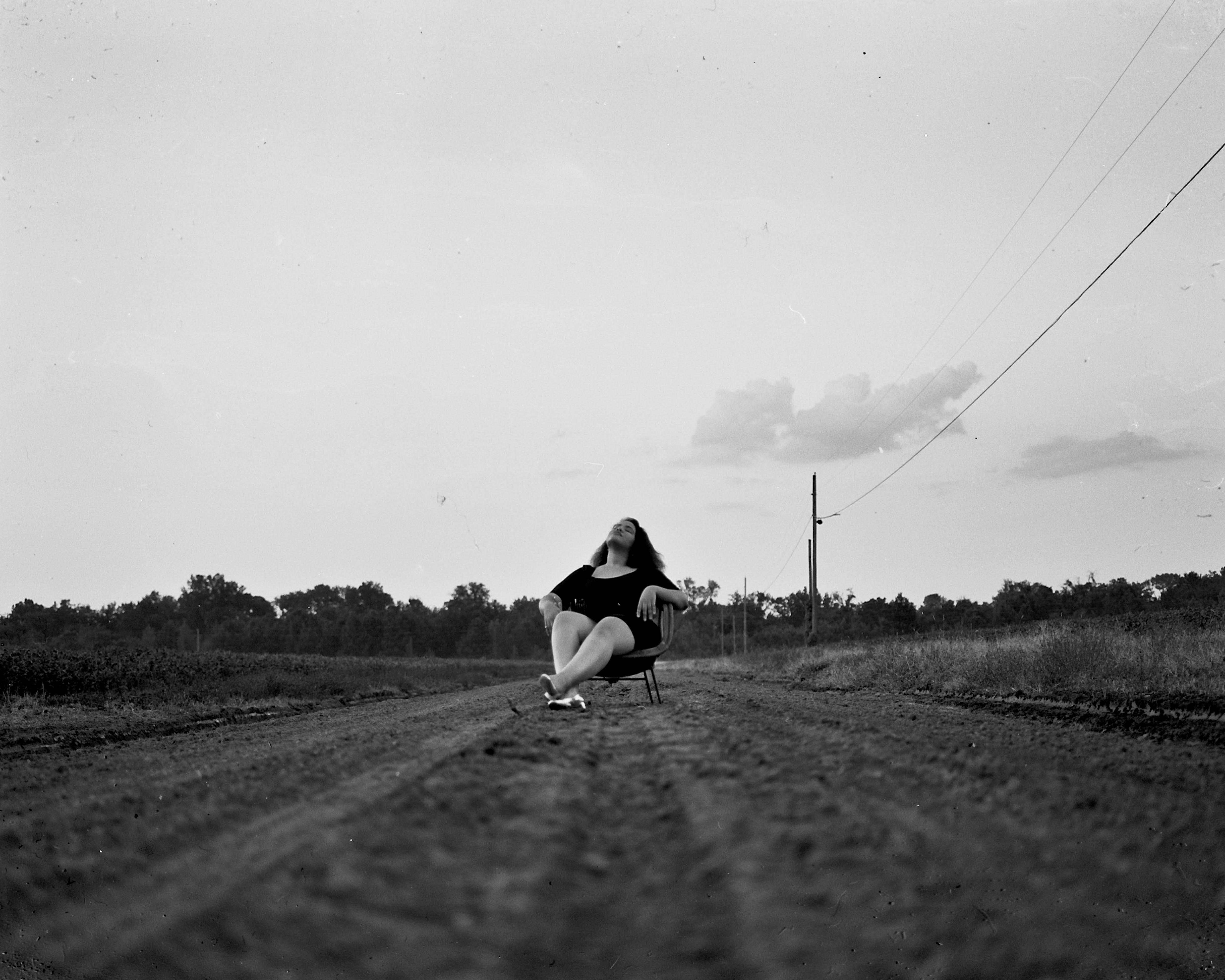 Grayscale Photography of Woman Sits on Chair on Pathway