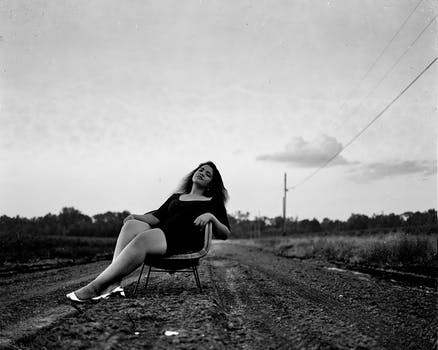 Black And White Photography Of Woman On Chair Road