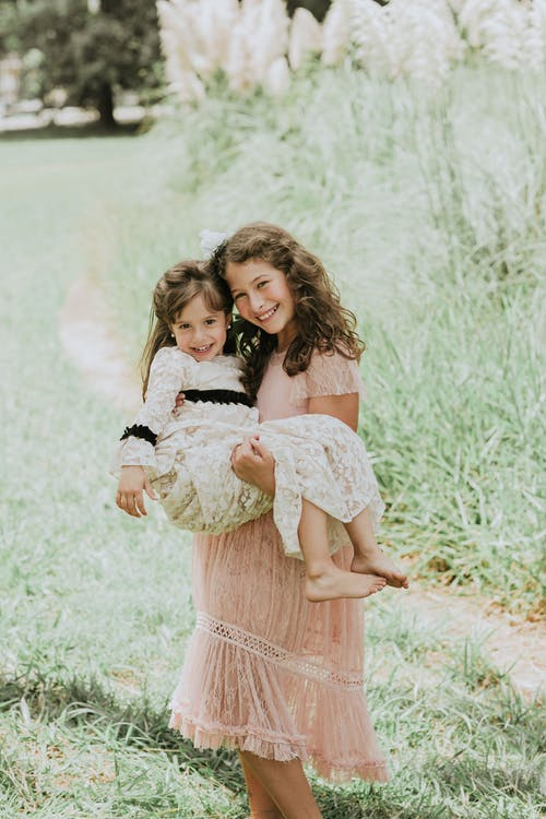 Photo of a Girl in a Pink Dress Carrying Her Little Sister while Looking at the Camera