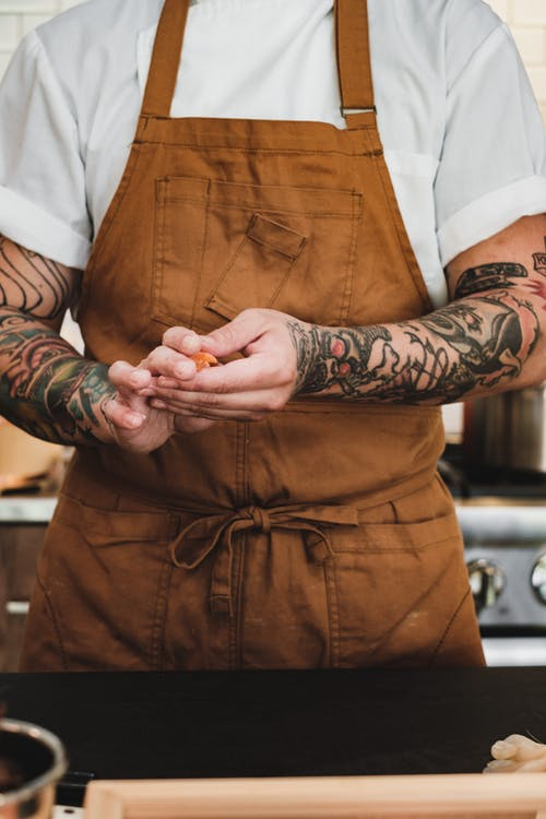 Close up on mans tattooed arms in apron