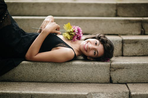 Photo of a Woman Lying on a Concrete Step while Holding a Bunch of Flowers