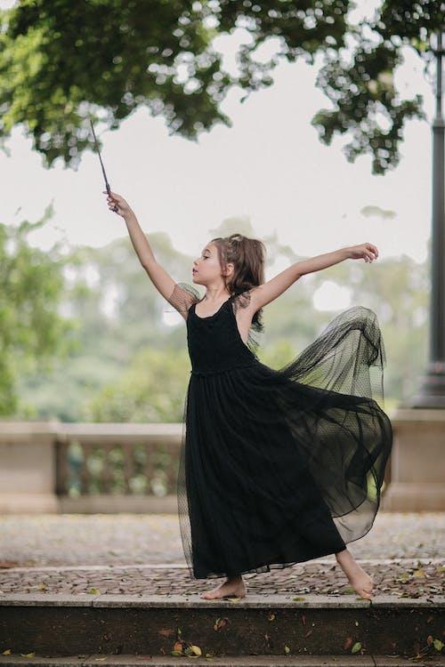 Girl in black dress posing with magic wand