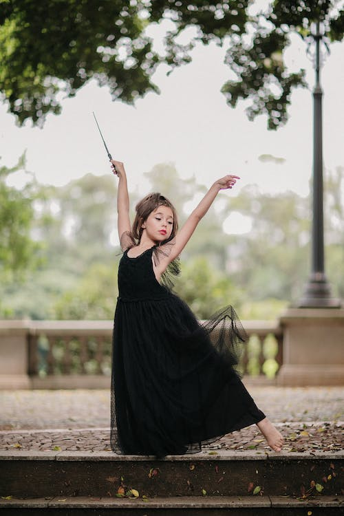 Portrait of girl in dress posing with magic wand