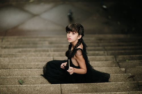 High-Angle Shot of a Girl in a Black Dress Sitting on Concrete Stairs