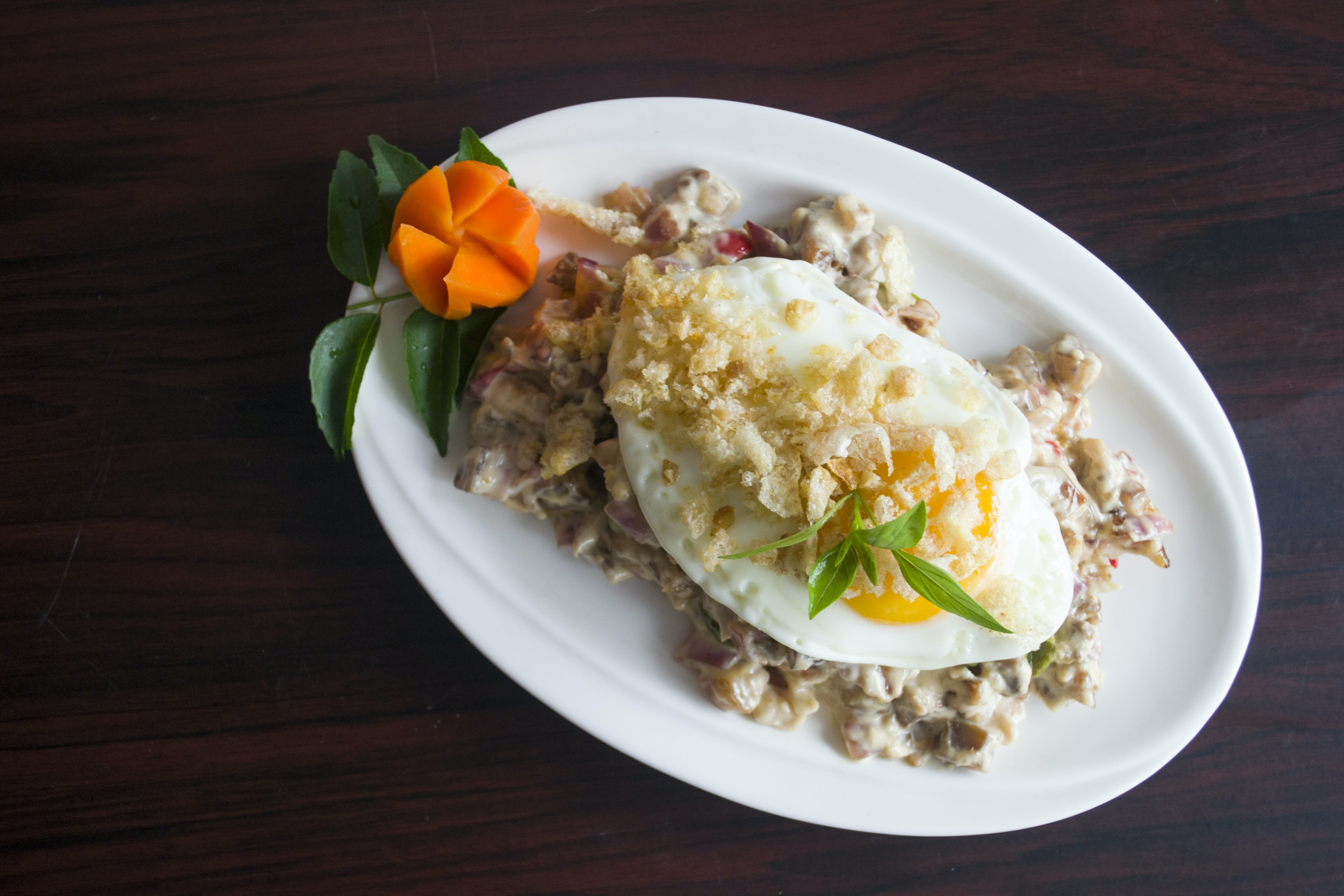 Serving of Marinated Meat With Sunny Side-up Egg and Slice of Carrot in Oval White Ceramic Plate