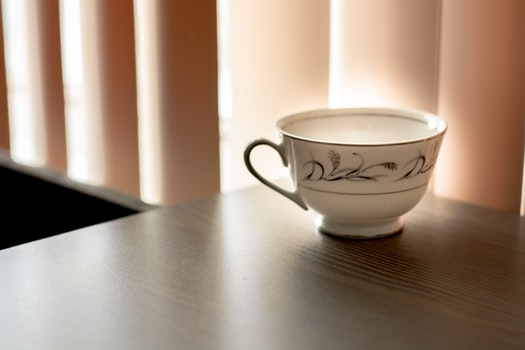 White and Black Ceramic Teacup on Brown Wooden Surface