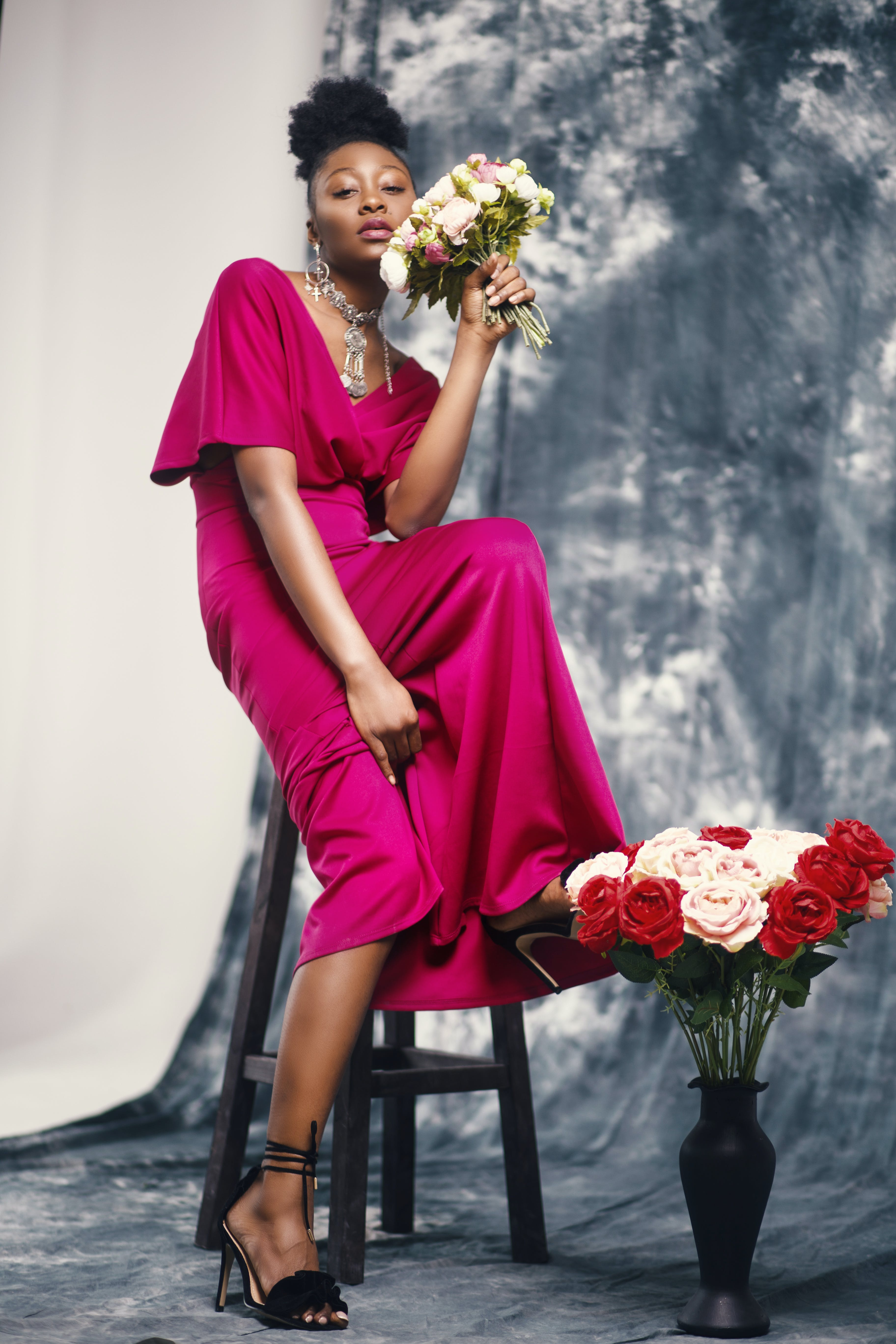 Woman in Pink Maxi Dress Holding Bouquet of Flowers