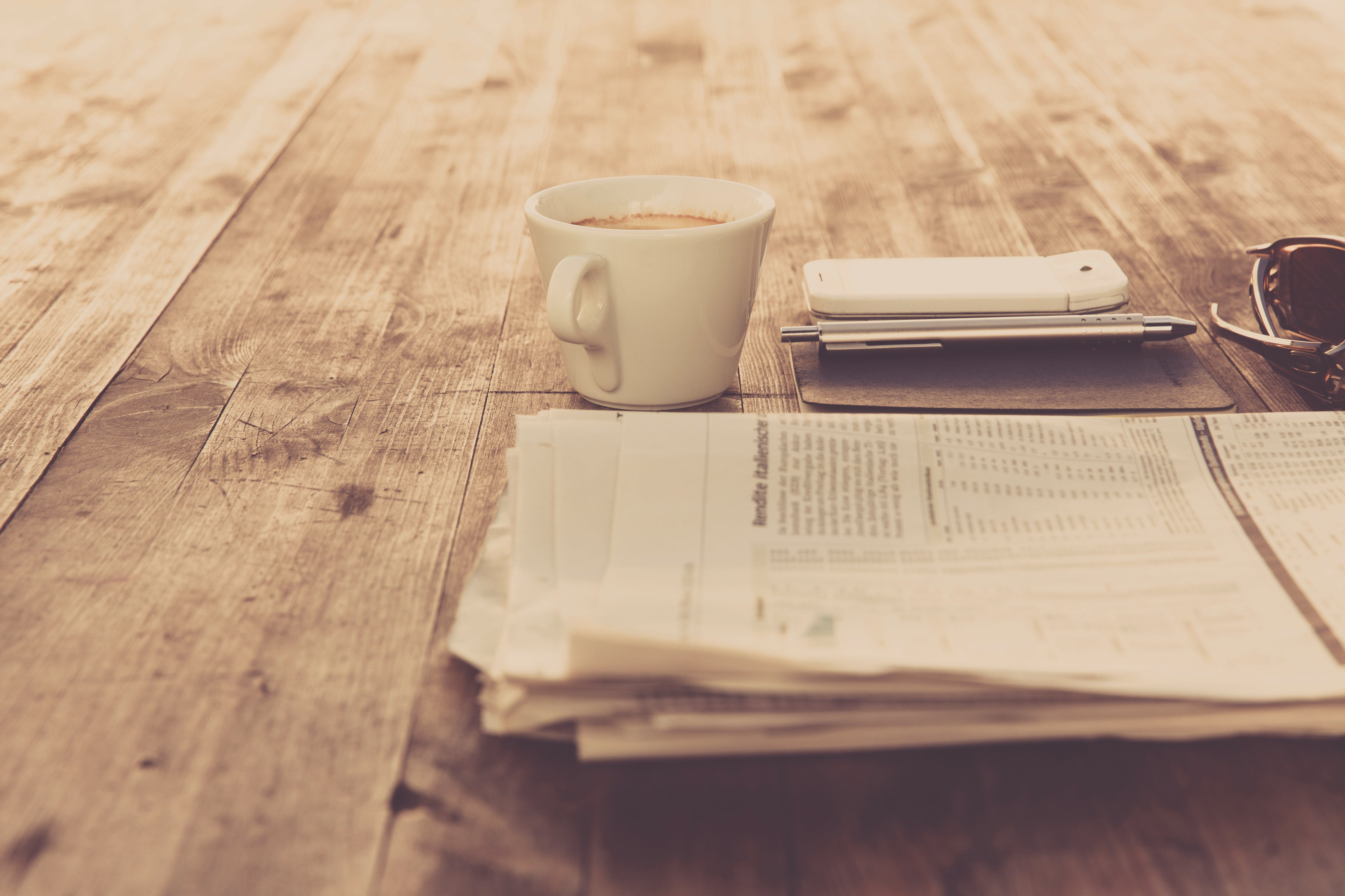 Newspaper and White Ceramic Cup on Brown Wooden Table