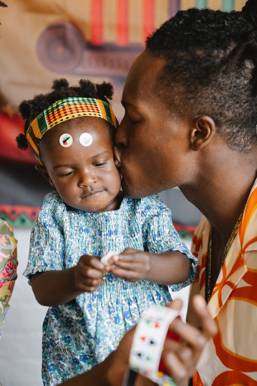 African father kissing his daughter