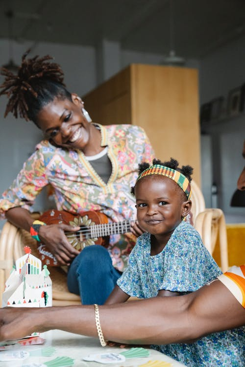 African American mother playing ukulele to her daughter