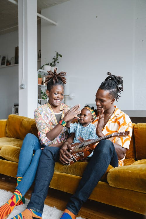 African family sitting on couch and playing guitar