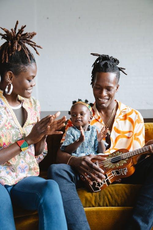 African American family playing ukulele