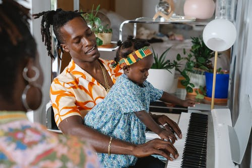 African father teaching his daughter to play piano