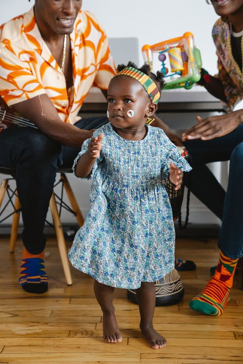 Cute little girl standing barefoot before her parents and clapping hands
