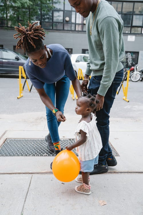 Family walking in street and little girl holding yellow balloon in hand