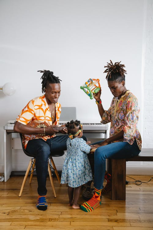 African man playing ukulele with his family