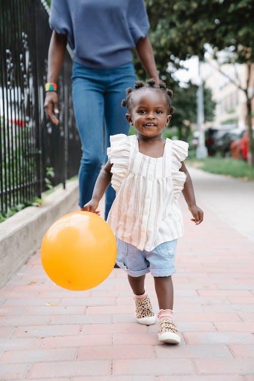 Cute little girl walking on sidewalk with yellow balloon