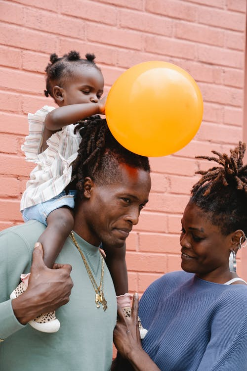African child girl sitting on her father shoulders and holding balloon