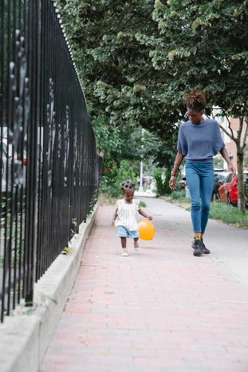 Little girl walking with her mother on sidewalk and playing balloon
