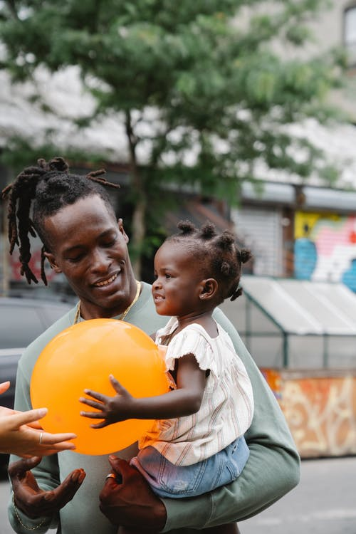 African father having his daughter in his arms