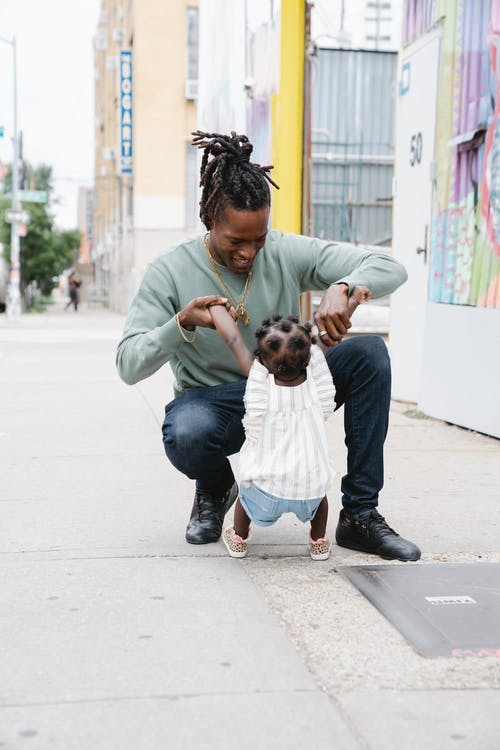 Father playing with his daughter on the street