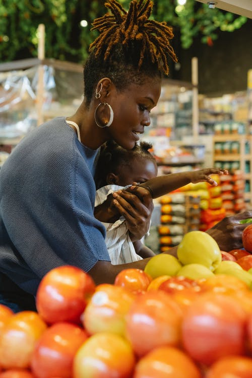 Woman picking fruits with daughter in grocery store