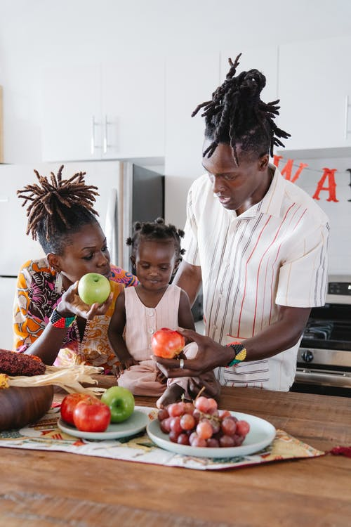 An african American family in a kitchen picking fruits