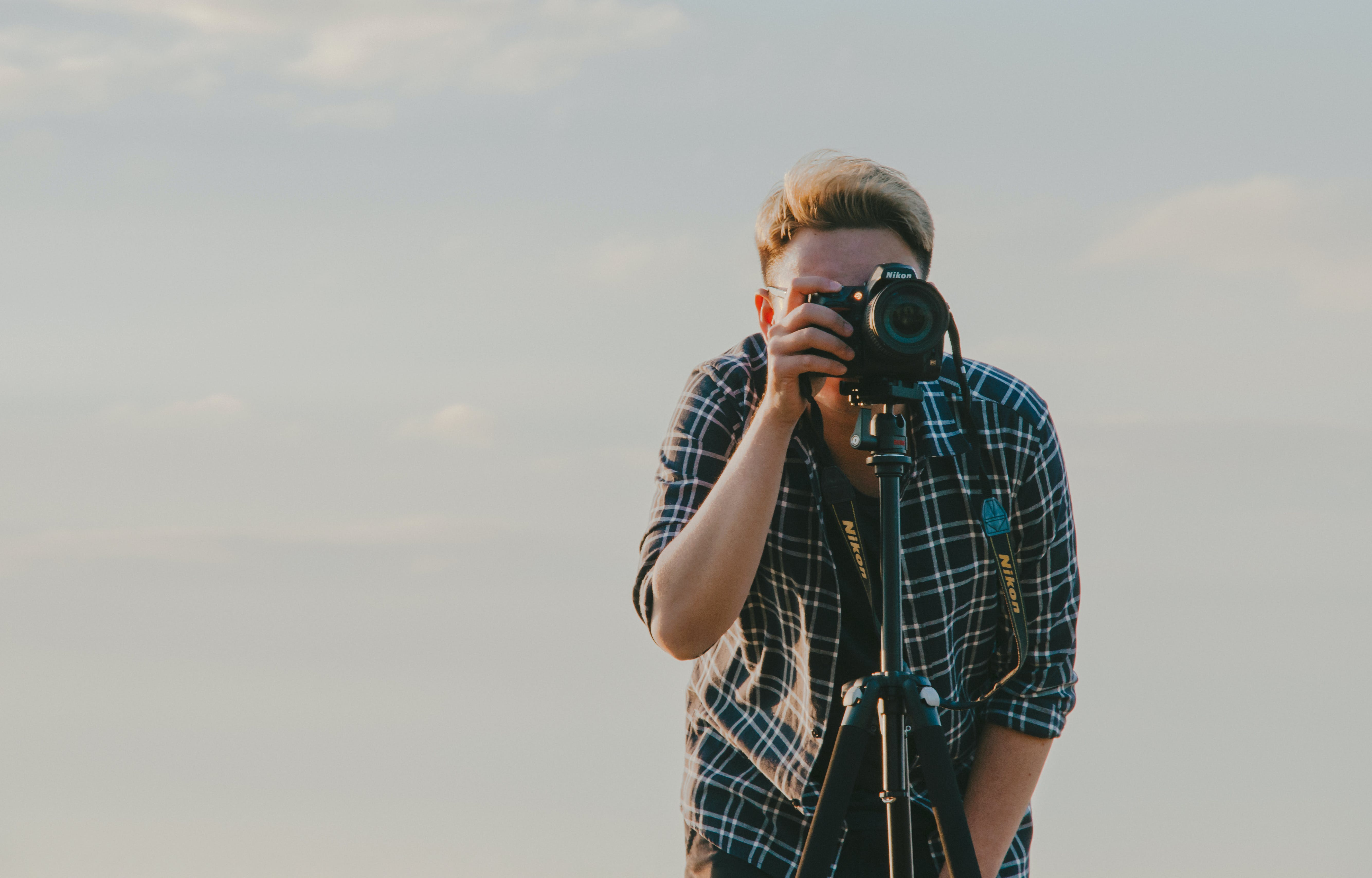 Man Holding Dslr Camera With Tripod