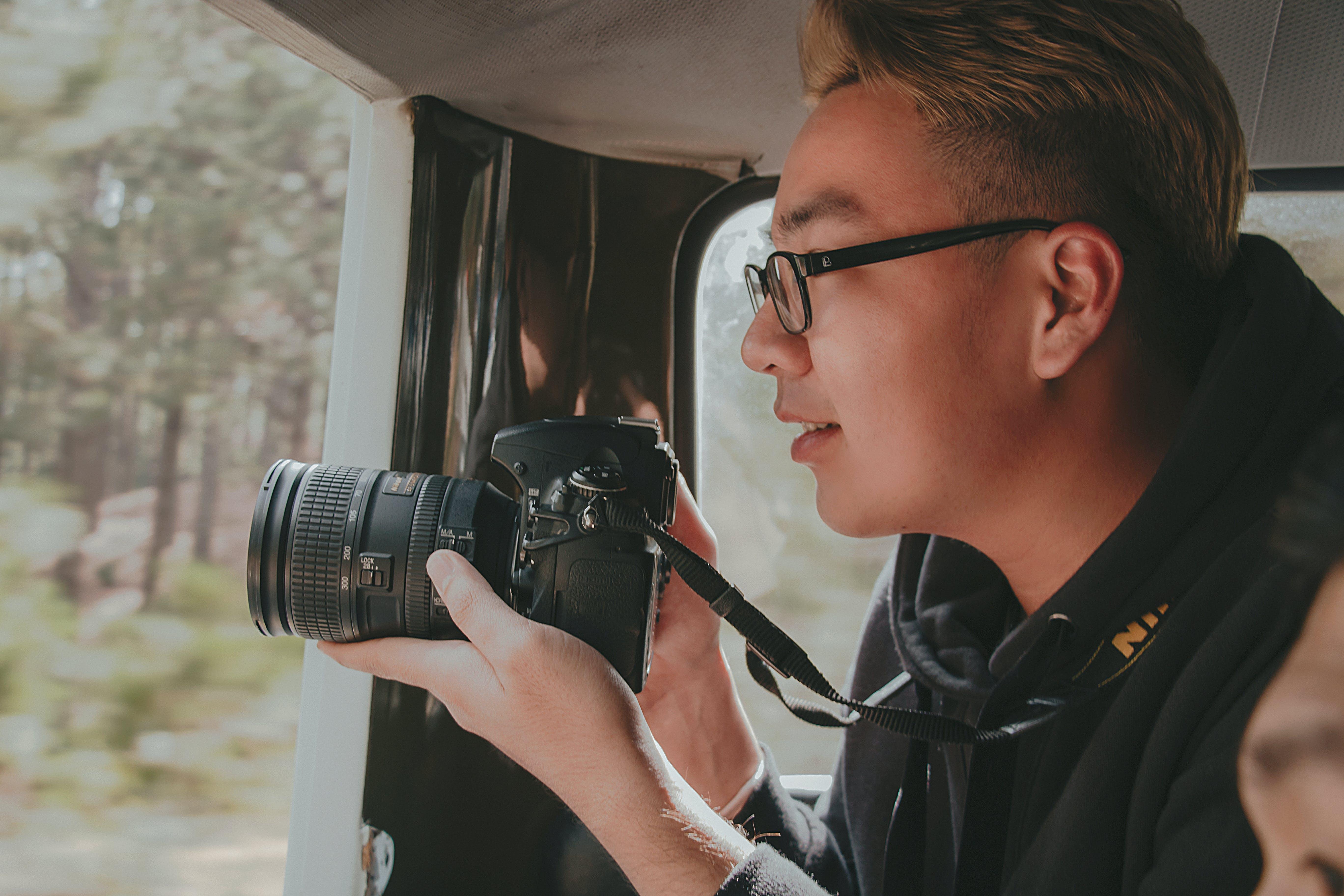 Photo of Man Holding Nikon Dslr Camera