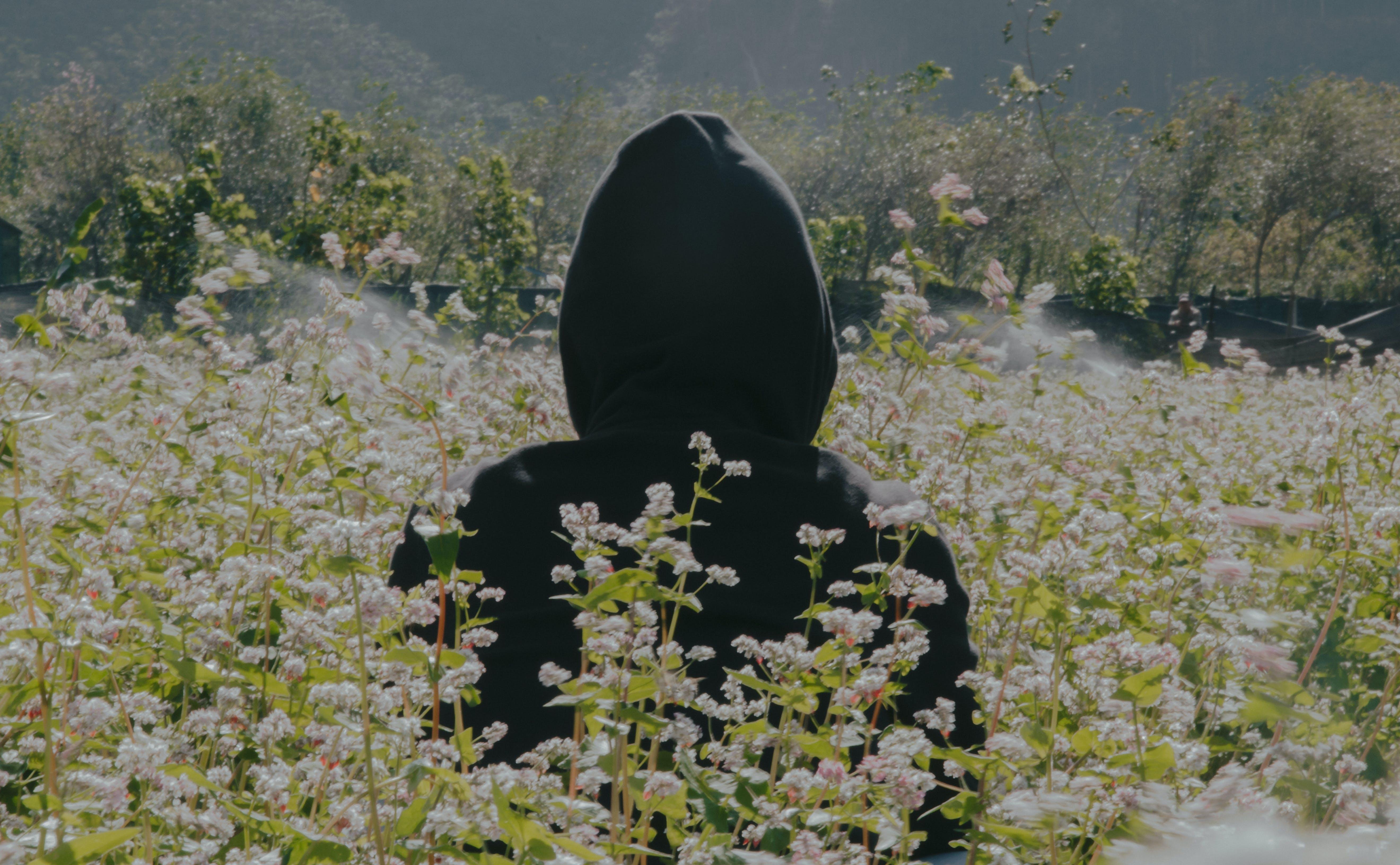 Photo of Person Wearing Black Hoodie Standing On Flower Field