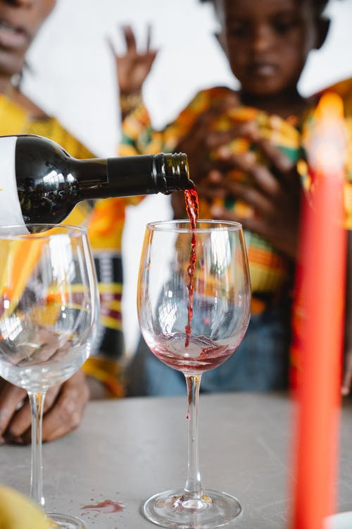 Close-Up Photo of a Person Pouring Red Wine into a Wine Glass