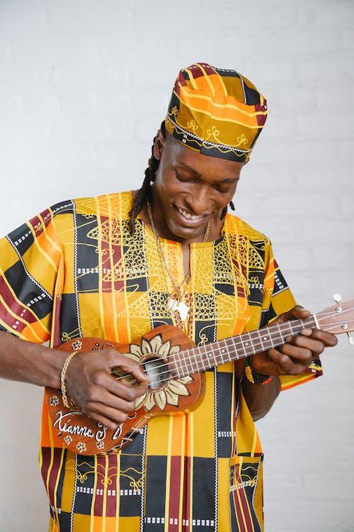 Photos gratuites de homme afro-américain, instrument de musique, jaune
