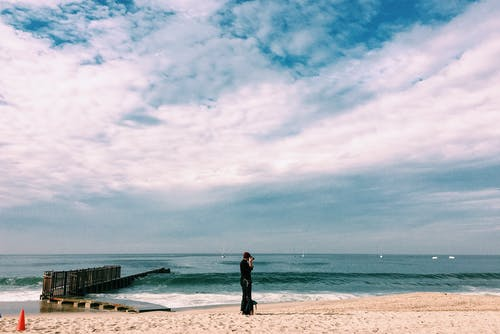 Person in Black Top Standing on Seashore Under White Clouds