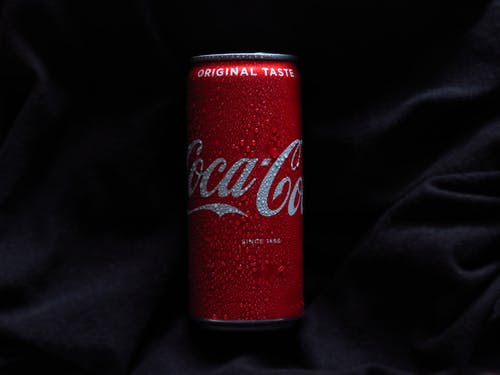 Close-Up Photo of a Coca Cola Can on a Black Textile