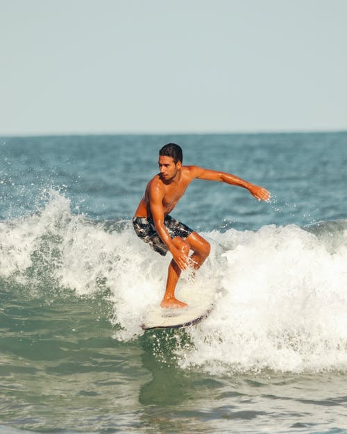 Photo of a Topless Man Surfing at the Ocean