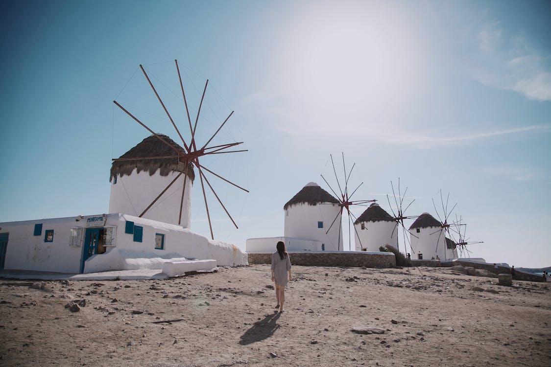 Woman Wearing Grey Dress Walking In Front Of Windmill Under Blue Sky