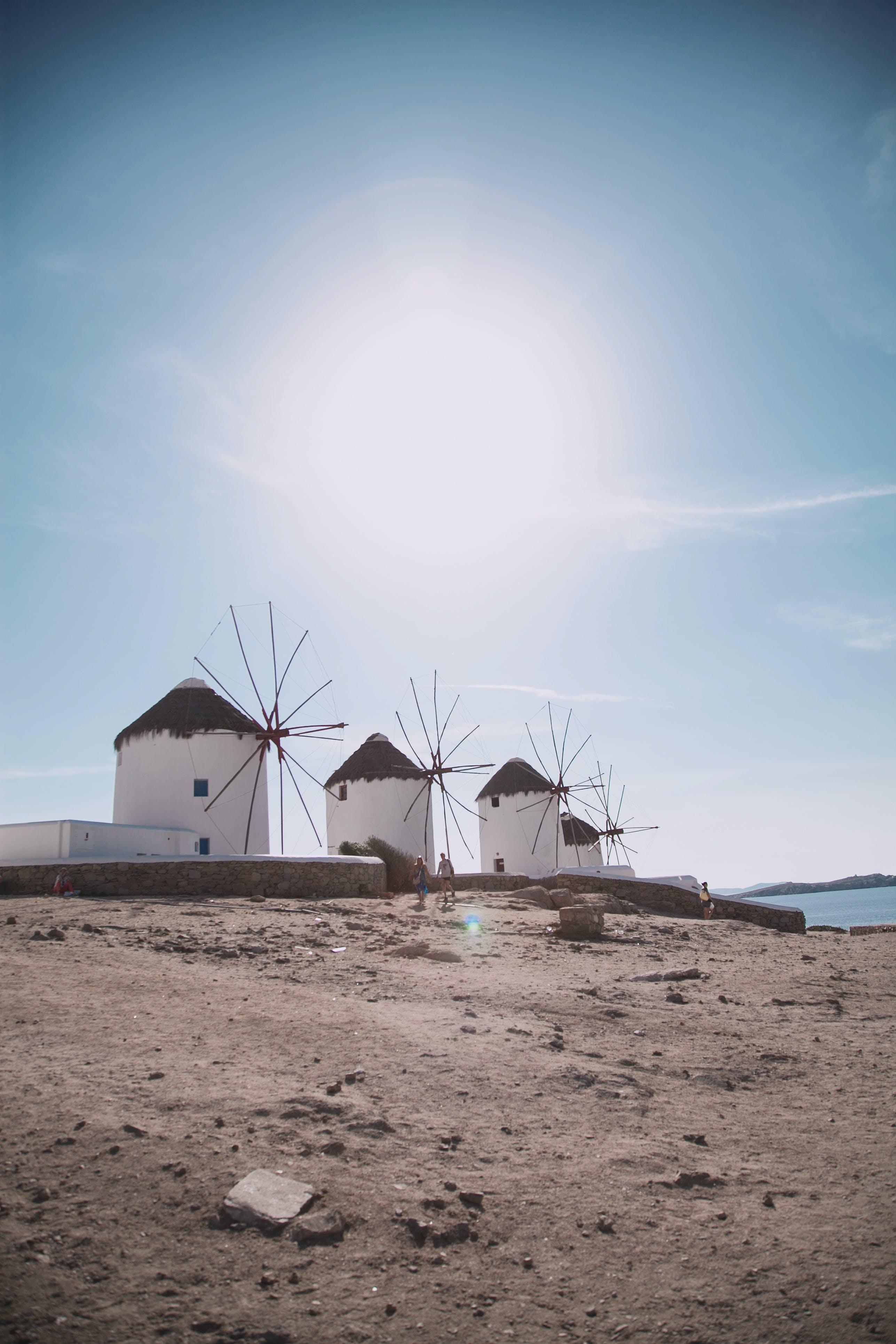 Four Windmills Near Body Of Water
