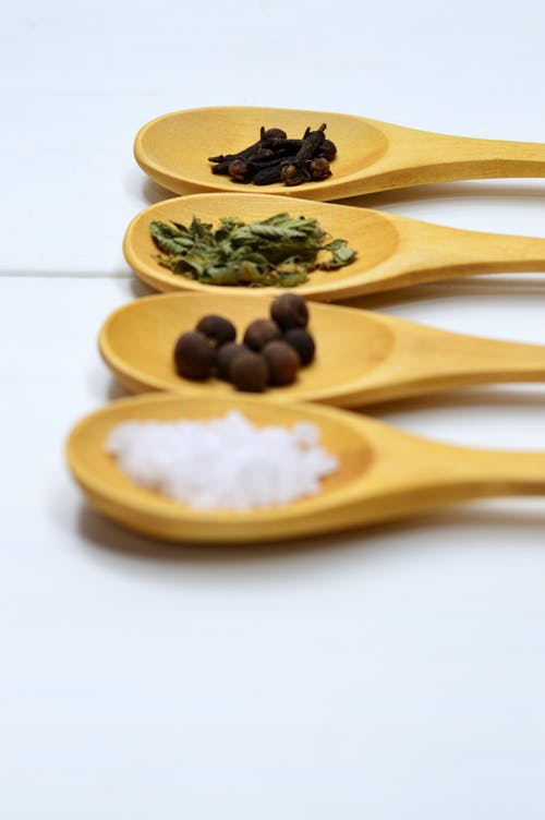 Four Assorted Spices on Brown Wooden Spoon
