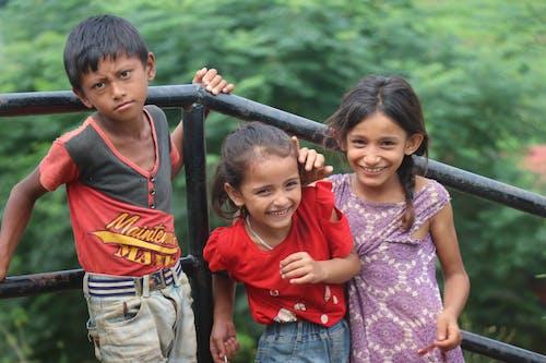 Kids Standing Near the Metal Railings