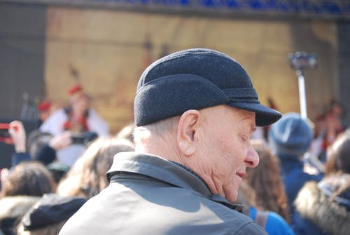 Man Wearing Cap And Grey Coat Surrounded With People
