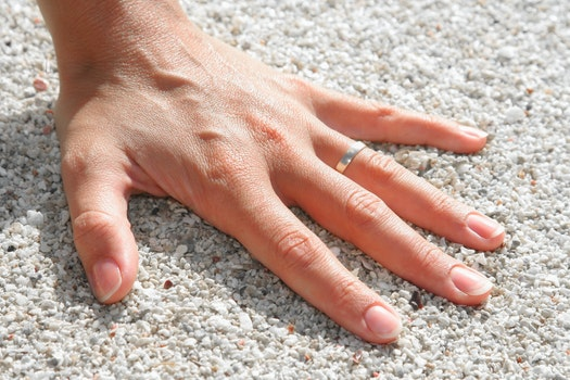 Lef Humand Hand Wearing Silver Ring on the Soil