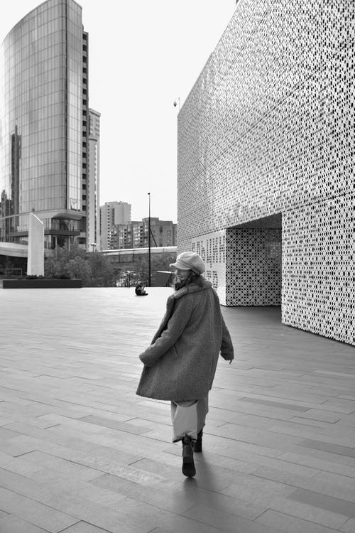 Grayscale Photo of a Woman in a Coat Walking at a City