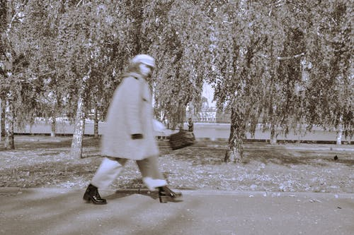 Person in White Coat Walking on Gray Concrete Road