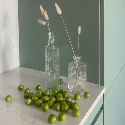 Green plums laying on kitchen counter