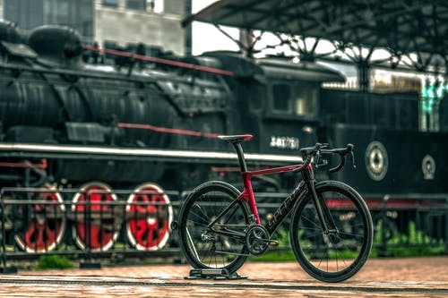 Black And Red Road Bike Near Black Train