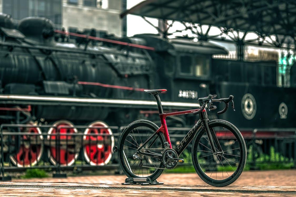 Black And Red Road Bike Near Black Train