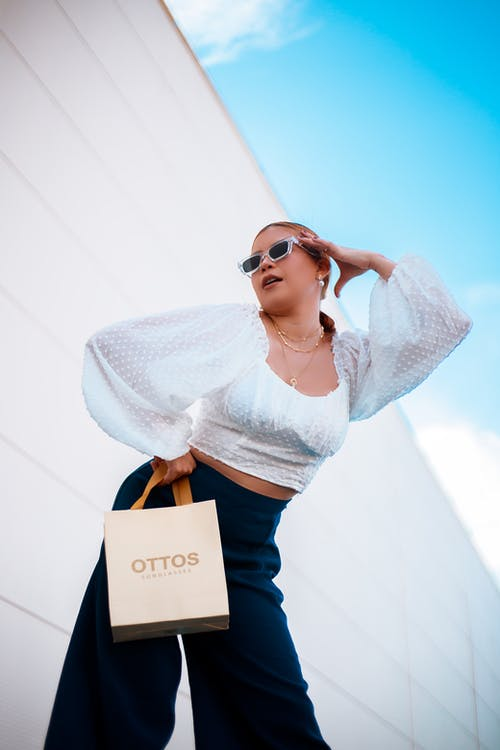 Woman in White Long Sleeve Shirt and Blue Denim Jeans Holding Brown Paper Bag