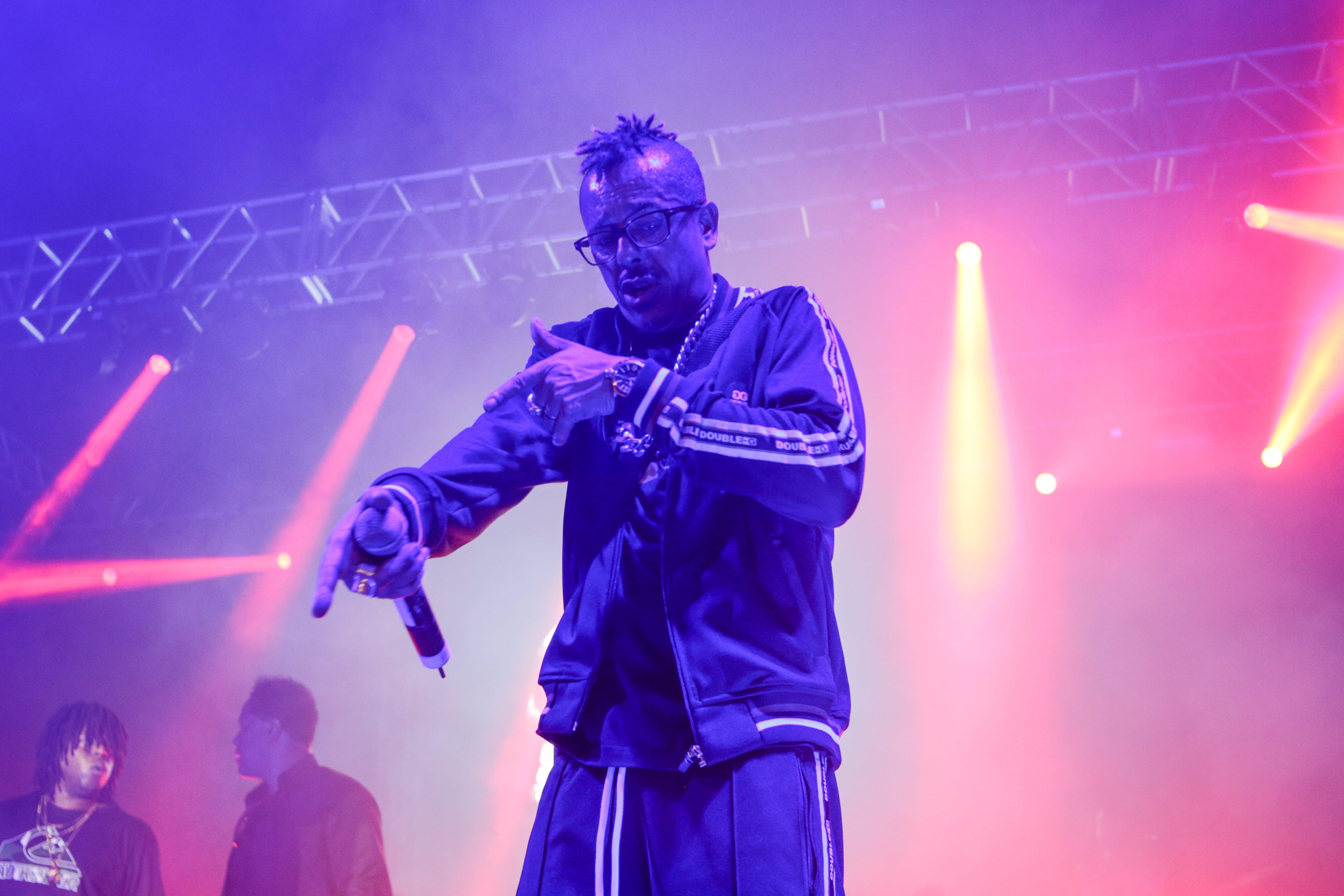 Man Wearing Zip Jacket Having Concert on Stage
