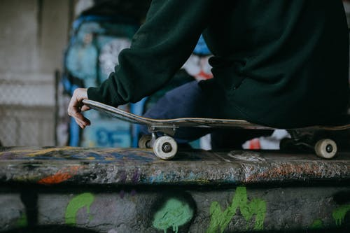 Close up on man hand holding skateboard