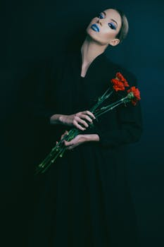 Woman in Black Long-sleeved Dress Holding Red Flowers
